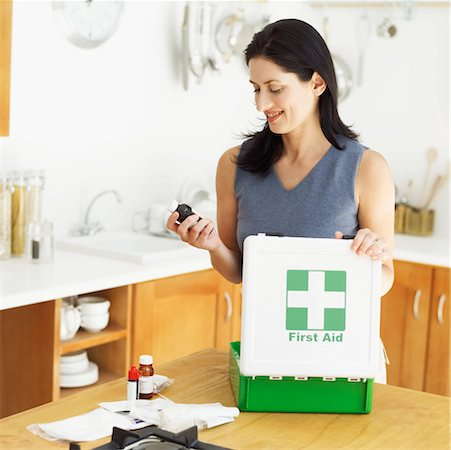 young woman looking at a bottle of medicine from a first aid kit Stock Photo - Premium Royalty-Free, Code: 618-00488487