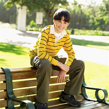 Portrait of a teenager (12-13) smiling sitting on a park bench Stock Photo - Premium Royalty-Free, Code: 618-00494616