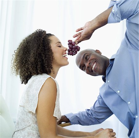 Young man feeding a Young woman a bunch of grapes Stock Photo - Premium Royalty-Free, Code: 618-00495339