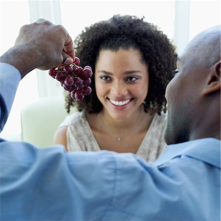 Young man holding a bunch of grapes in front of a young woman Stock Photo - Premium Royalty-Free, Code: 618-00495341