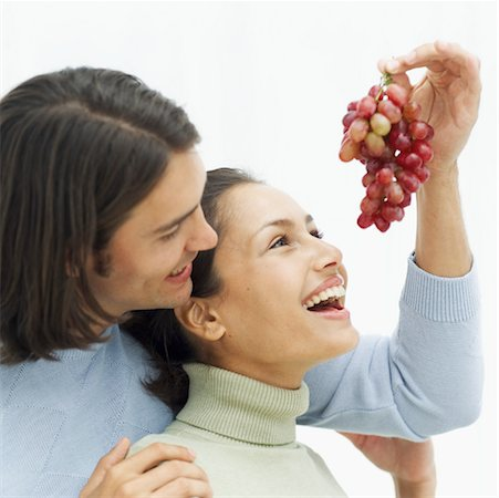 close-up of a young man feeding grapes to a young woman Stock Photo - Premium Royalty-Free, Code: 618-00495776