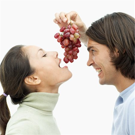 Side profile of a young man feeding grapes to a young woman Stock Photo - Premium Royalty-Free, Code: 618-00495779