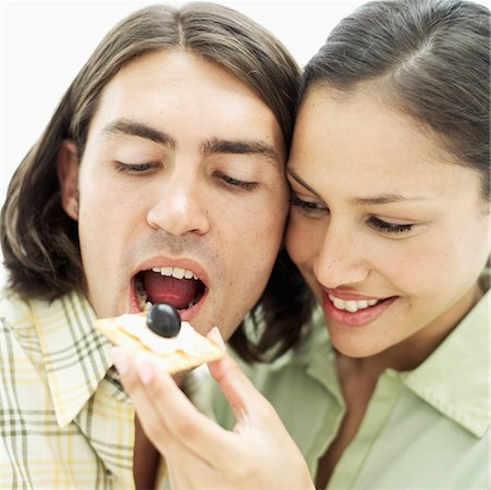 Close-up of a young woman feeding a young man a cracker with cheese Stock Photo - Premium Royalty-Free, Code: 618-00495818