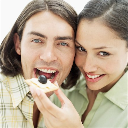 close-up of a young woman feeding a cracker with cheese to a young man Stock Photo - Premium Royalty-Free, Code: 618-00495819