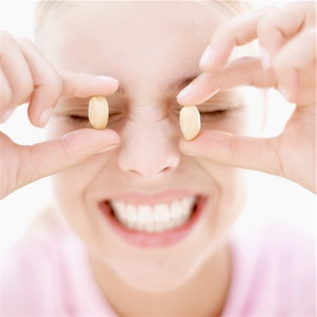 close-up of a teenage girl holding peanuts up to her eyes Stock Photo - Premium Royalty-Free, Code: 618-00496524