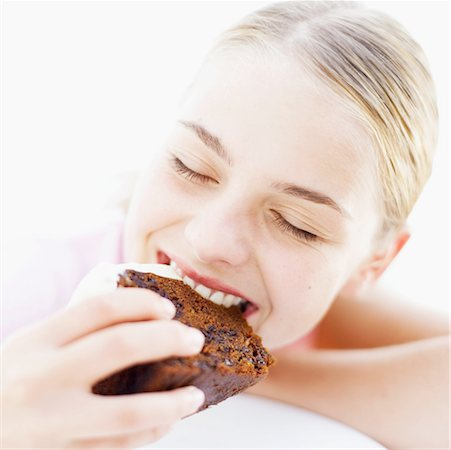 close-up of a teenage girl eating a slice of chocolate cake Stock Photo - Premium Royalty-Free, Code: 618-00496537