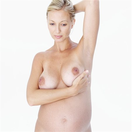 close-up of a naked mid adult pregnant woman examining her breast Stock Photo - Premium Royalty-Free, Code: 618-00497172