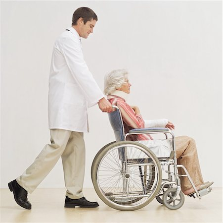 male doctor pushing a senior woman in a wheelchair Stock Photo - Premium Royalty-Free, Code: 618-00498220