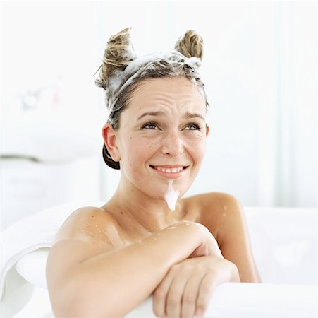 Close-up of a young woman sitting in a bathtub with her hair shaped like horns Stock Photo - Premium Royalty-Free, Code: 618-00506130
