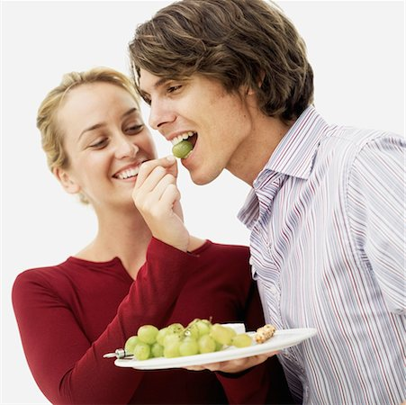 close-up of a young woman feeding grapes to a young man Stock Photo - Premium Royalty-Free, Code: 618-00506689