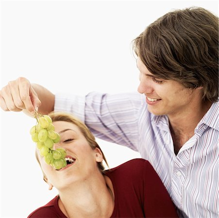 Young man feeding grapes to a Young woman Stock Photo - Premium Royalty-Free, Code: 618-00506683