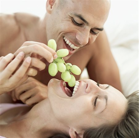 man feeding a woman grapes in bed Stock Photo - Premium Royalty-Free, Code: 618-00503454