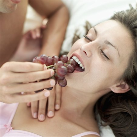 Close-up of a young man's hands feeding a young woman grapes in bed Stock Photo - Premium Royalty-Free, Code: 618-00503455