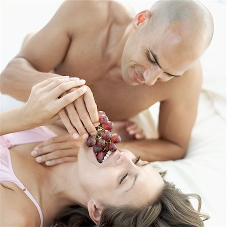 Young man feeding a Young woman grapes in bed Stock Photo - Premium Royalty-Free, Code: 618-00503456