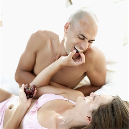 Young woman feeding a young man grapes in bed Stock Photo - Premium Royalty-Free, Code: 618-00503457