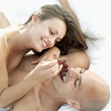 Young woman feeding a young man grapes in bed Stock Photo - Premium Royalty-Free, Code: 618-00503458