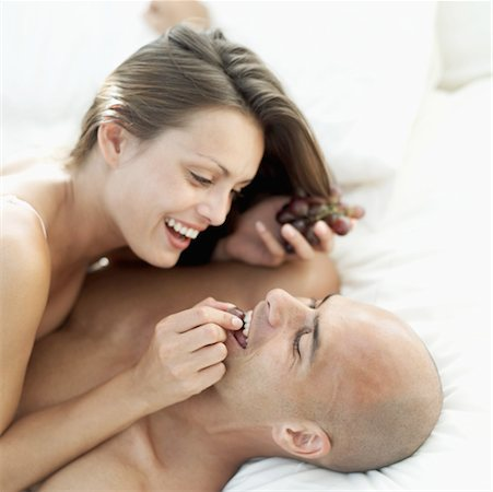 A young woman lying on top of A young man feeding him grapes Stock Photo - Premium Royalty-Free, Code: 618-00503459