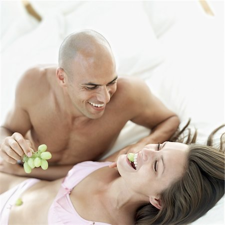 portrait of a young man feeding grapes to a woman lying down Stock Photo - Premium Royalty-Free, Code: 618-00503451