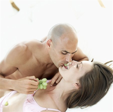 Young couple sharing grapes with each other in bed Stock Photo - Premium Royalty-Free, Code: 618-00503452