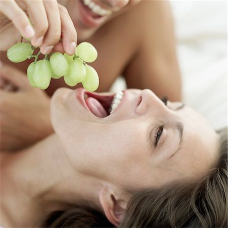 close-up of a young man feeding a young woman grapes Stock Photo - Premium Royalty-Free, Code: 618-00503453