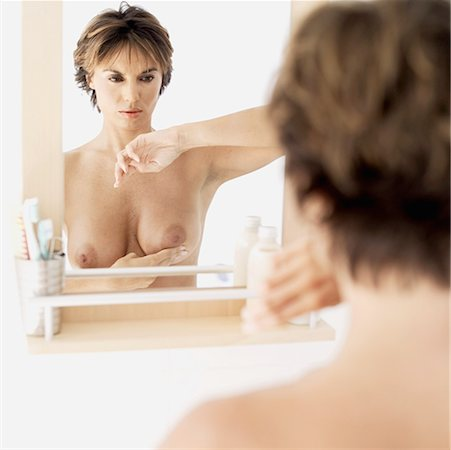 rear view of a naked mid adult woman examining her breast in the mirror Stock Photo - Premium Royalty-Free, Code: 618-00503496