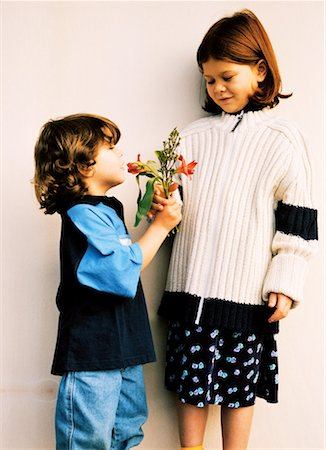 Young girl giving flower to another girl (4-8) Stock Photo - Premium Royalty-Free, Code: 618-00513650