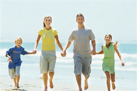 portrait of parents running with their children on the beach Stock Photo - Premium Royalty-Free, Code: 618-00689842