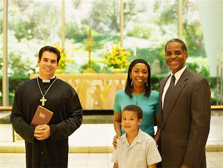 portrait of parents and their son standing with a priest Stock Photo - Premium Royalty-Free, Code: 618-00690066