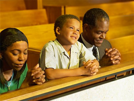 parents and their son praying in church Stock Photo - Premium Royalty-Free, Code: 618-00690074