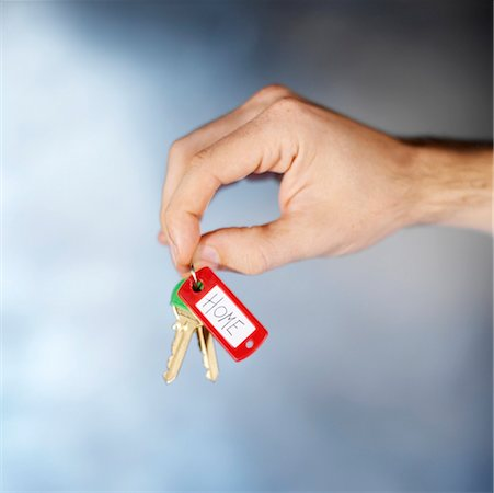 finger holding a key - close-up of a person's hand holding a key ring Stock Photo - Premium Royalty-Free, Code: 618-00692537