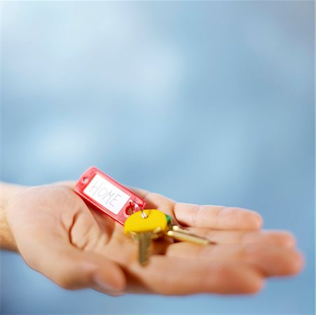 finger holding a key - close-up of a person's hand holding a key ring Stock Photo - Premium Royalty-Free, Code: 618-00692538