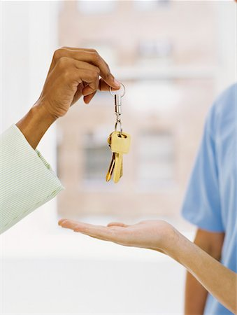 finger holding a key - close-up of a person's hand offering a key ring to another person's hand Stock Photo - Premium Royalty-Free, Code: 618-00692574