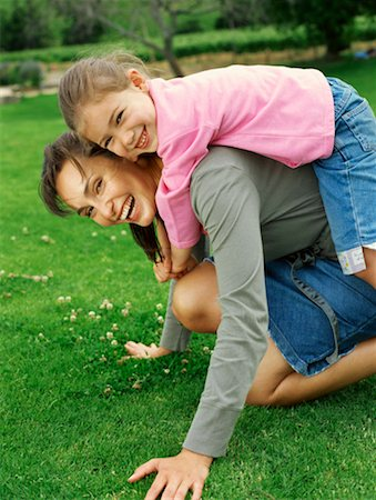 Portrait of a daughter riding piggyback on her mother Stock Photo - Premium Royalty-Free, Code: 618-00785104