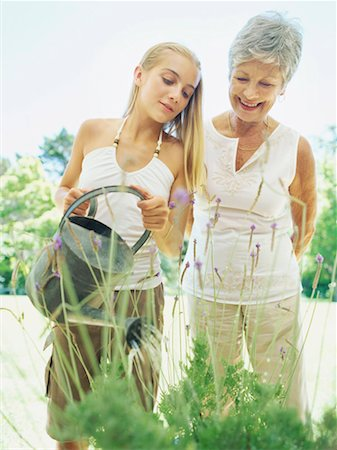 Grandmother looking at her granddaughter watering plants Stock Photo - Premium Royalty-Free, Code: 618-00786519