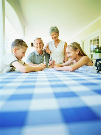 Grandchildren playing with mobile phones and grandparents in the background Stock Photo - Premium Royalty-Free, Code: 618-00786529