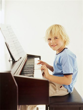 preteen  smile  one  alone - Side profile of a boy playing the piano Stock Photo - Premium Royalty-Free, Code: 618-00786630