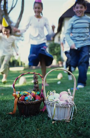 Girls and boys (7-10) running towards basket of Easter eggs on lawn Stock Photo - Premium Royalty-Free, Code: 618-01061847
