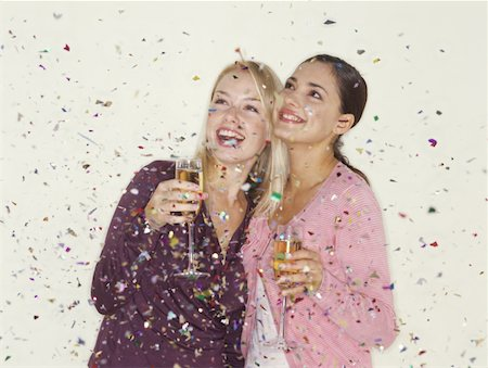 Two young women holding champagne and being showered in confetti Stock Photo - Premium Royalty-Free, Code: 618-01062711