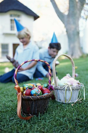 Two boys (7-9) sitting in garden, basket of Easter eggs in foreground Stock Photo - Premium Royalty-Free, Code: 618-01295359