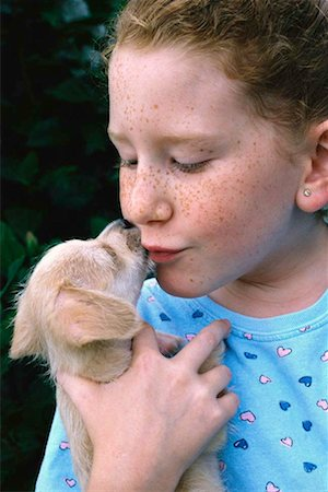 dog kissing girl - Red-headed girl being kissed by puppy Stock Photo - Premium Royalty-Free, Code: 618-01419709
