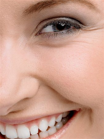 Young woman, smiling, portrait, close-up of eye, nose and mouth Stock Photo - Premium Royalty-Free, Code: 618-01549227