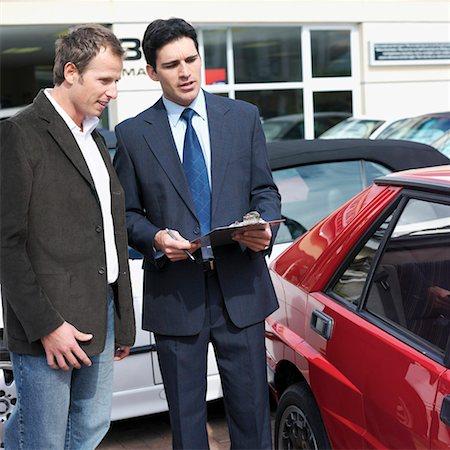 Car salesman talking with customer outdoors Stock Photo - Premium Royalty-Free, Code: 618-01738076