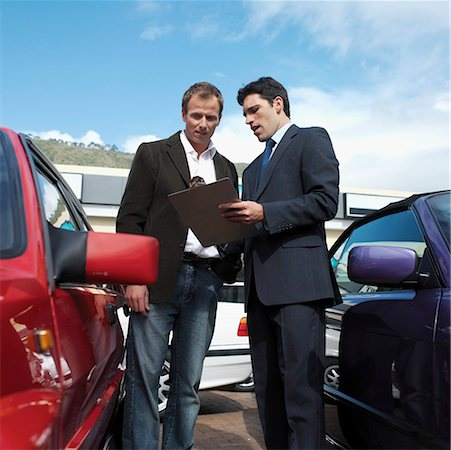Car salesman talking with customer, standing between two cars outdoors Stock Photo - Premium Royalty-Free, Code: 618-01738078