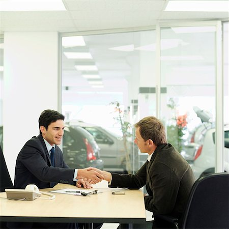 Car salesman shaking hands over desk with customer in car showroom Stock Photo - Premium Royalty-Free, Code: 618-01738079