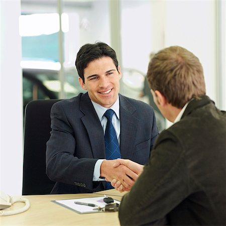 Car salesman shaking hands over desk with customer in car showroom Stock Photo - Premium Royalty-Free, Code: 618-01738080