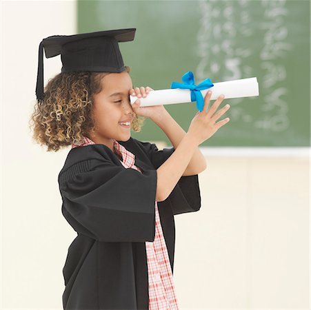 Girl (6-7) wearing university gown and mortar board looking through scroll Stock Photo - Premium Royalty-Free, Code: 618-01738387