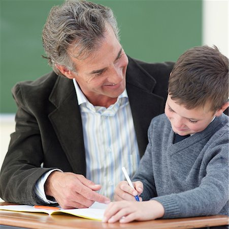 Teacher helping boy (8-9) with work in classroom Stock Photo - Premium Royalty-Free, Code: 618-01738394