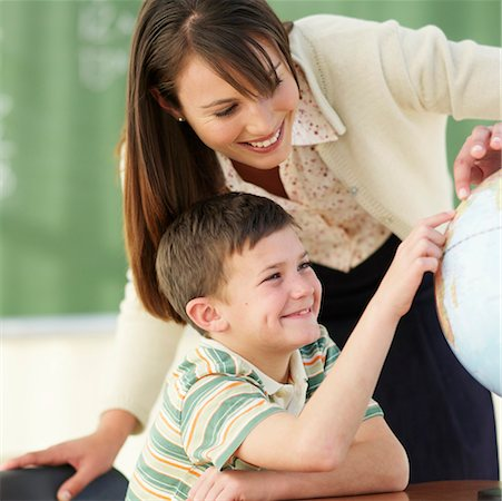 Teacher and boy (8-9) looking at globe in classroom Stock Photo - Premium Royalty-Free, Code: 618-01738397