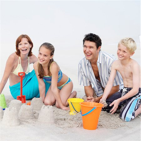 Family including boy and girl (11 13) building sandcastles and laughing Stock Photo - Premium Royalty-Free, Code: 618-01738751