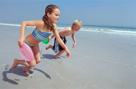 Boy and girl (11-13) running with flying disc on beach Stock Photo - Premium Royalty-Free, Code: 618-01738774